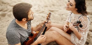 Couple singing to each other on the beach, take the love language quiz